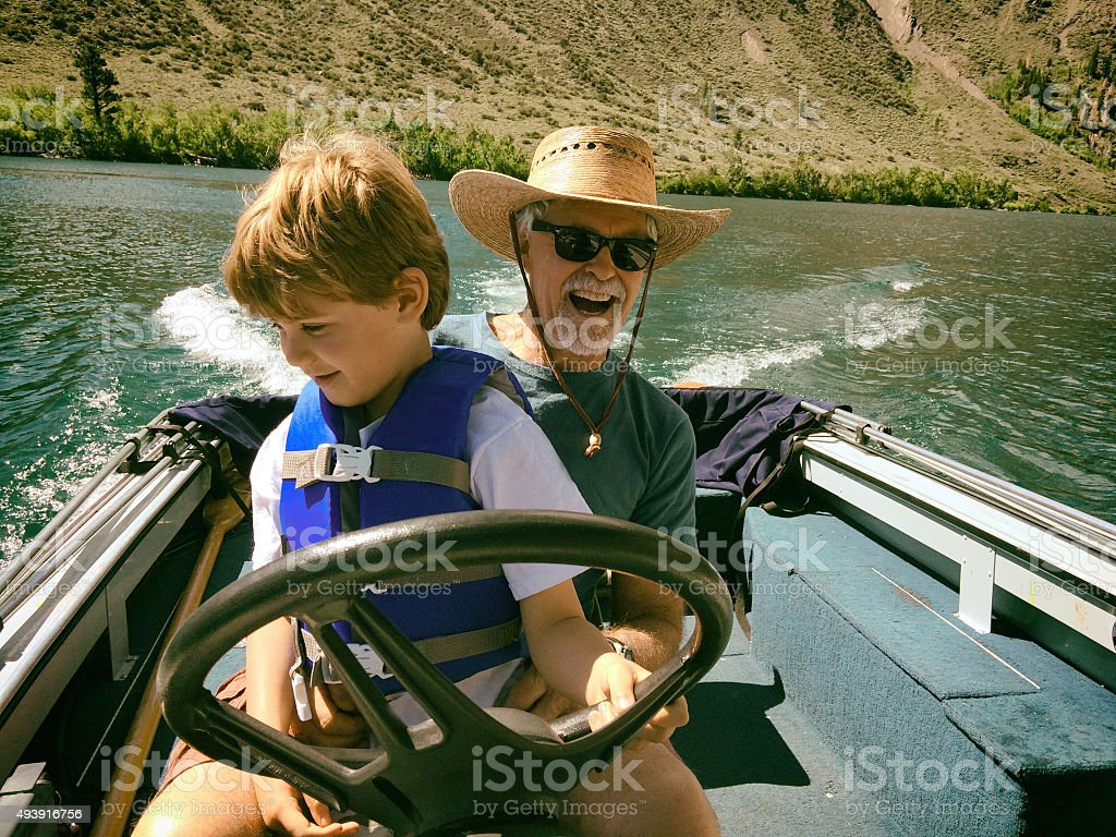 Child driving a boat with Grandpa stock photo