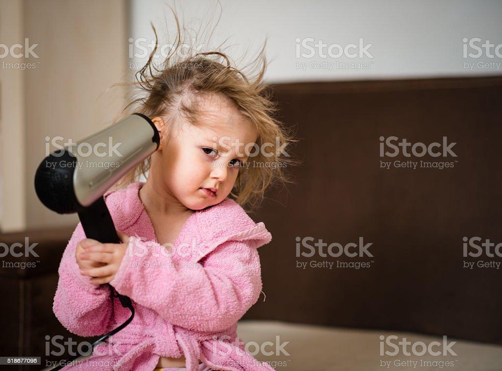 Child drying hair herself stock photo