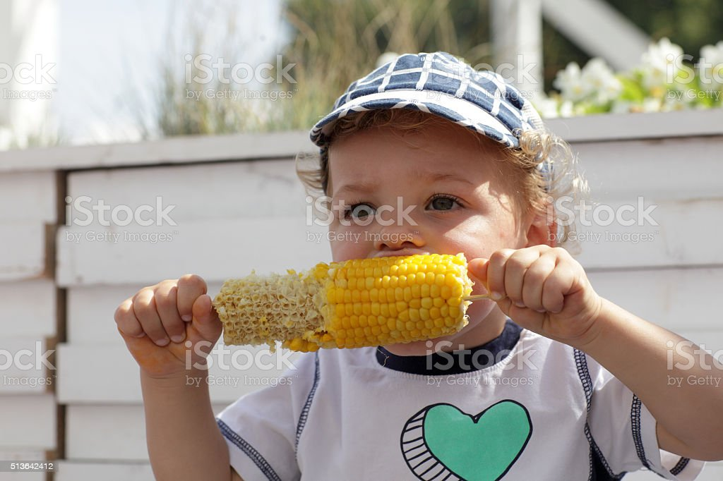 Child eating boiled corn stock photo
