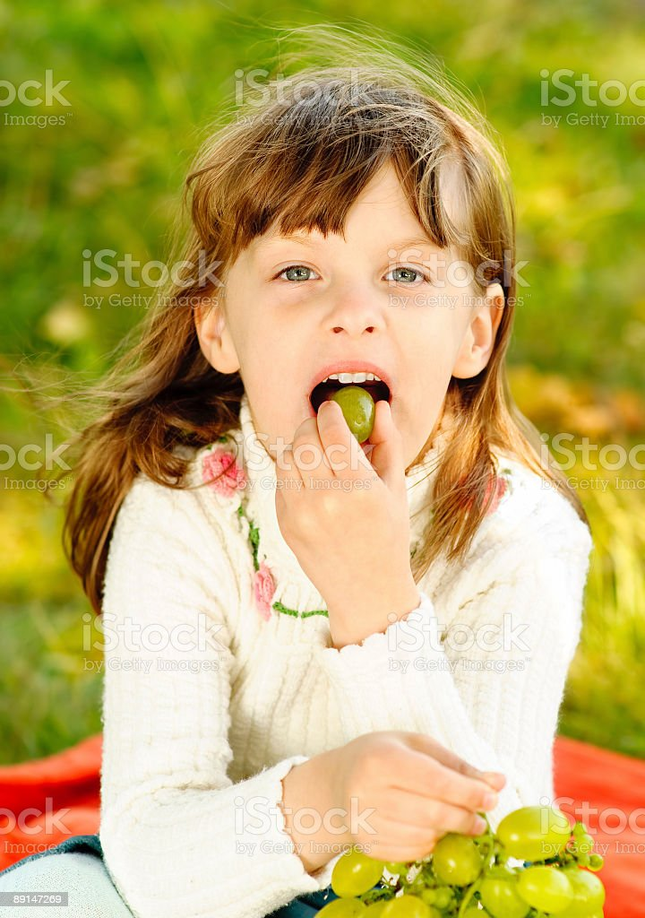 Child eats grapes royalty-free stock photo