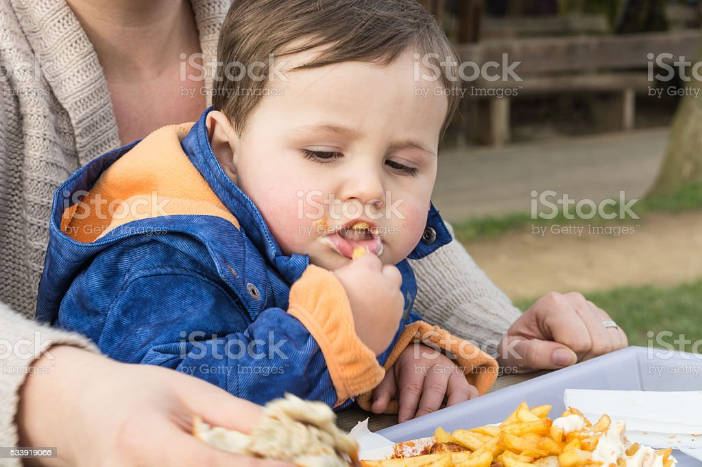 Child eats sausage with french fries stock photo
