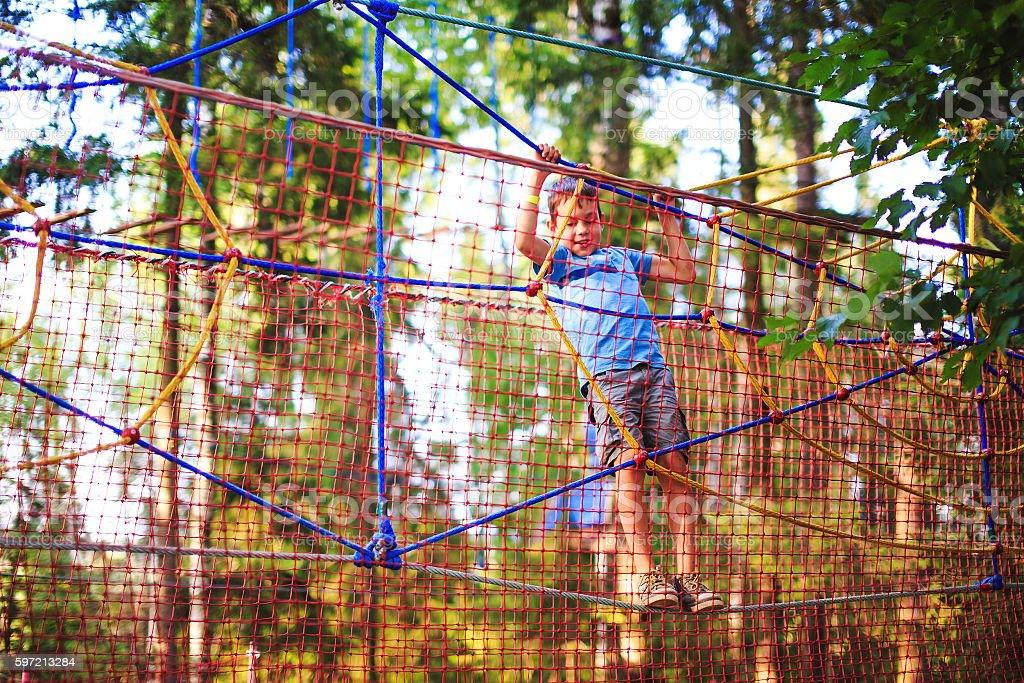 child enjoys climbing on the ropes playground stock photo