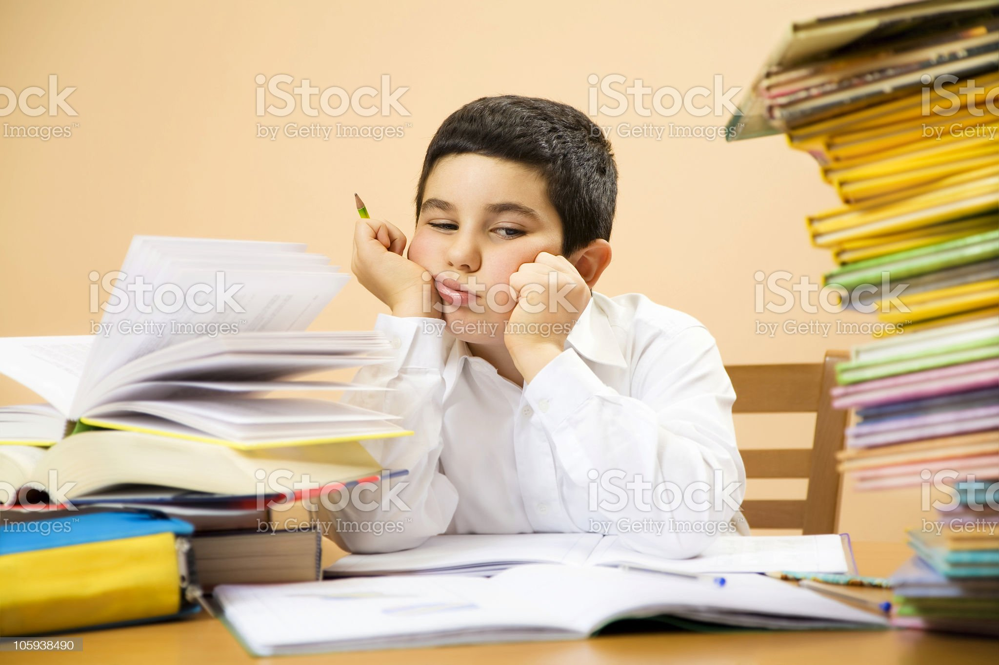Child exhausted and surrounded by books and homework royalty-free stock photo