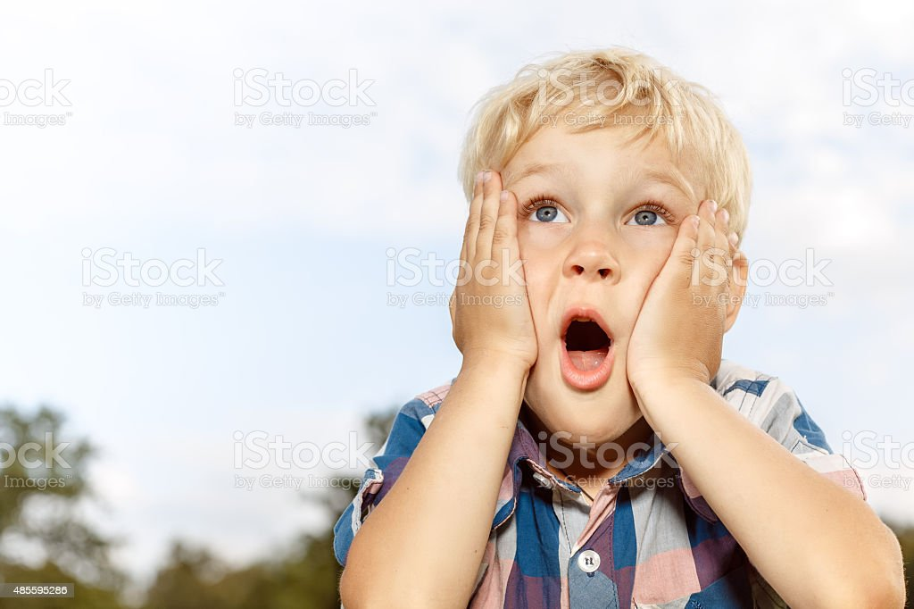 Child expressing surprise with hands on his face stock photo