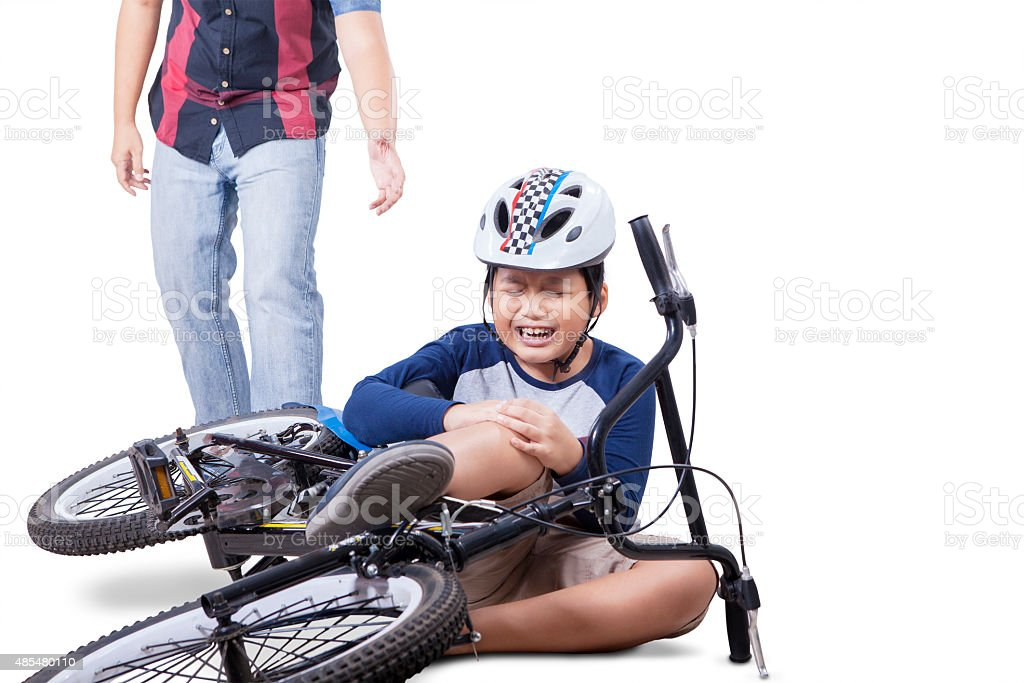 Child falling from his bike and crying stock photo