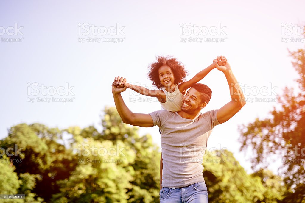 Child flying on father shoulders stock photo
