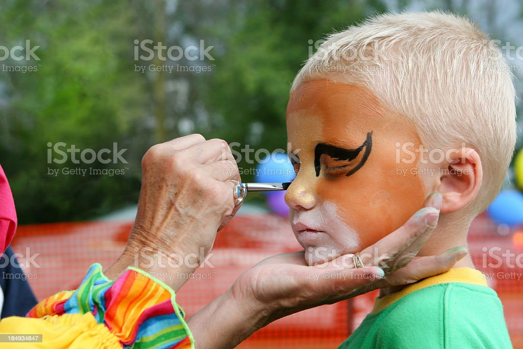 Child getting face painted royalty-free stock photo