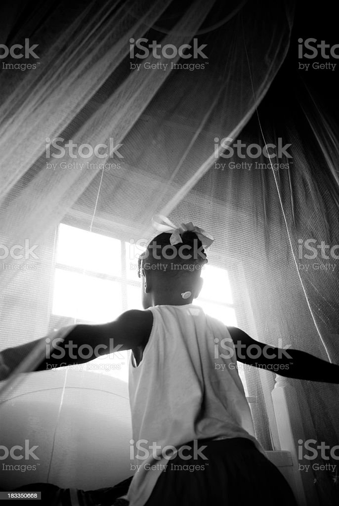 child getting out of bed and looking through window stock photo