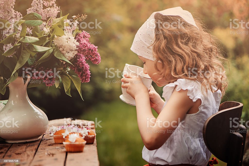 child girl at tea party in spring garden with lilacs stock photo