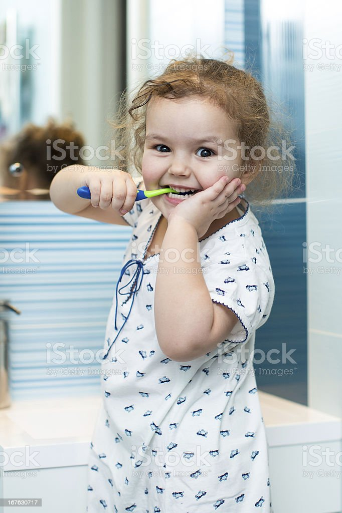 Child girl brushing teeth in bathroom royalty-free stock photo