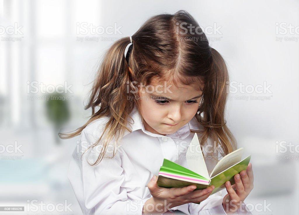 Child girl caucasian reading note book indoor. stock photo