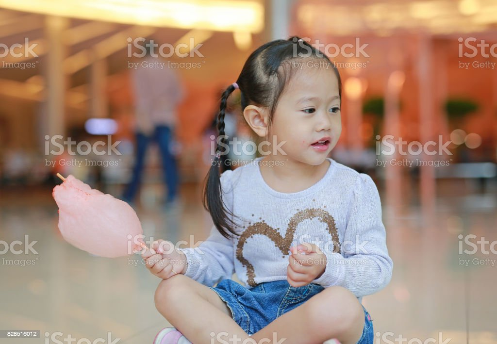 Child girl eating sweet spongy candy. stock photo