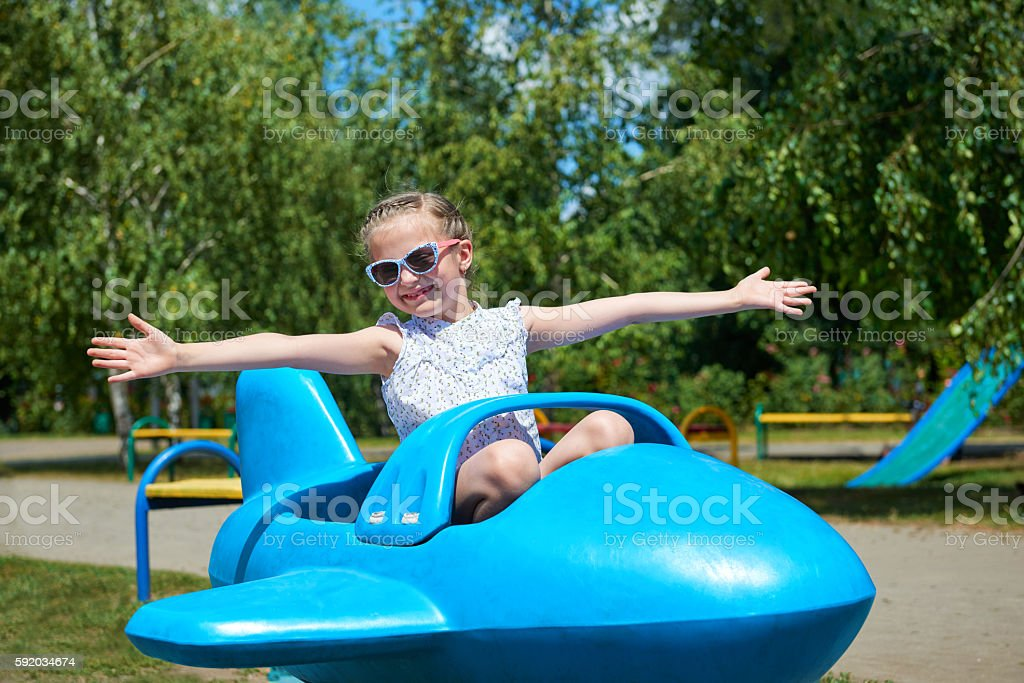 child girl fly on blue airplane attraction in amusement park stock photo