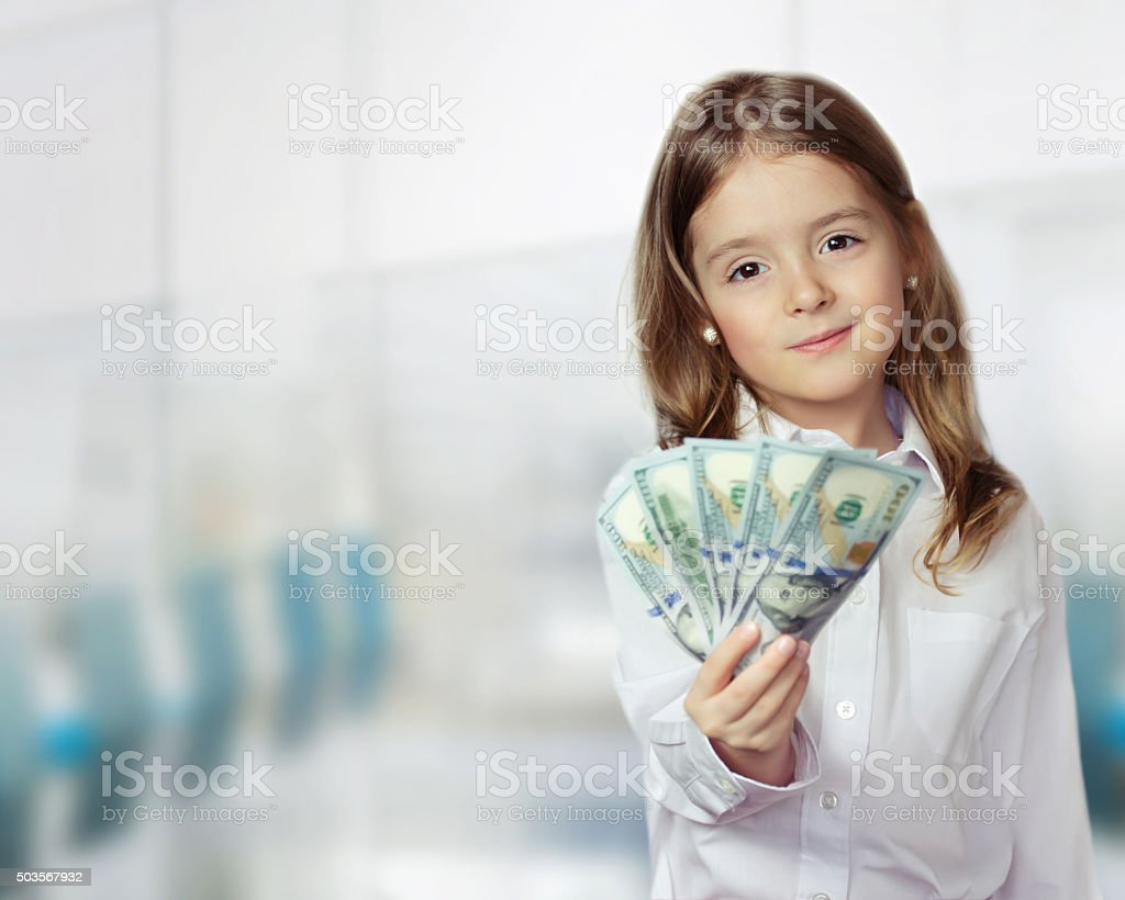 Child girl holding money in hands financial background. stock photo