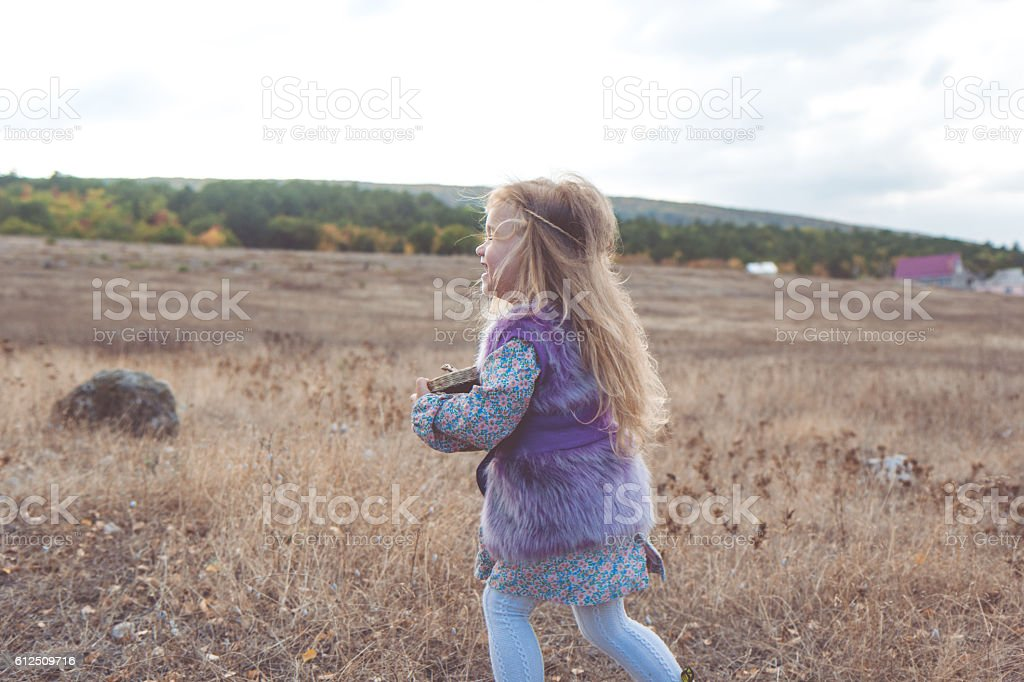 Child girl in autumn filed stock photo