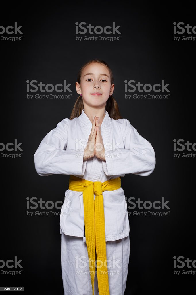 Child girl in karate suit with yellow belt show stance stock photo