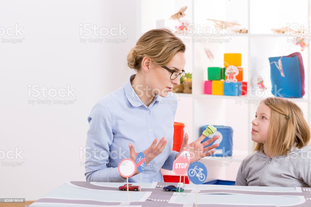 Girl learning traffic regulations with child psychologist in...