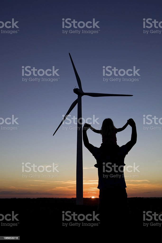 Child Girl on Dad's Shoulders near Wind Turbine at Sunset royalty-free stock photo