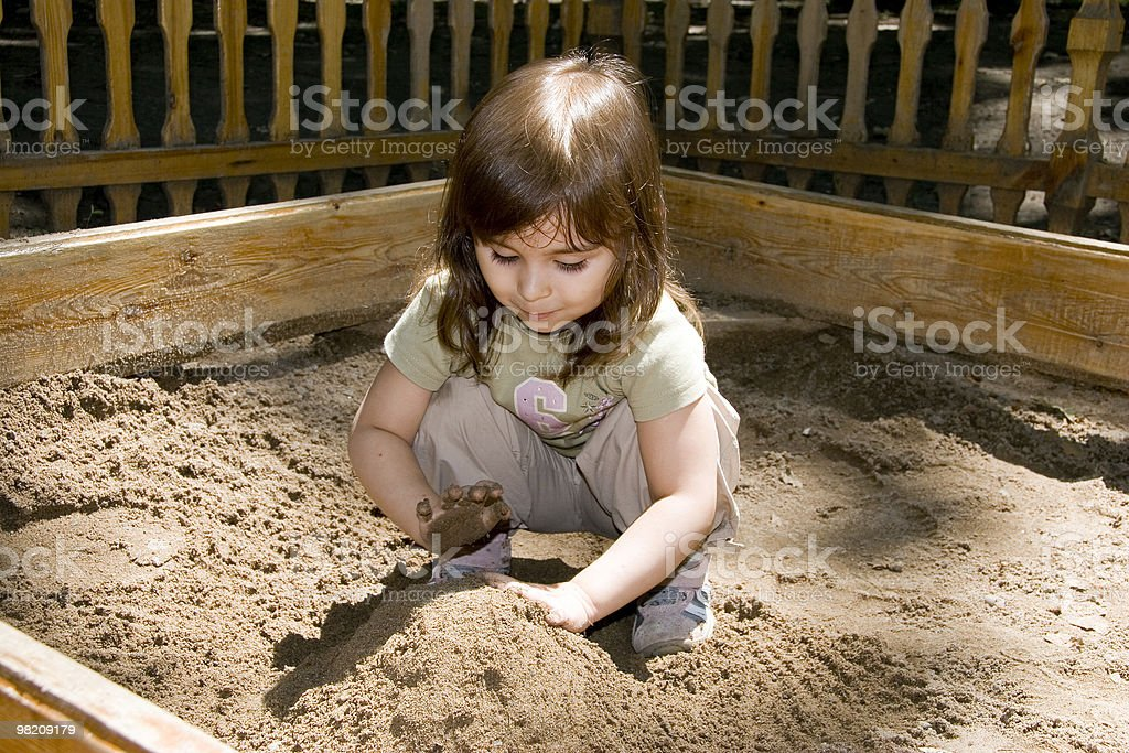 Child girl plaing at sand-box in summer park royalty-free stock photo