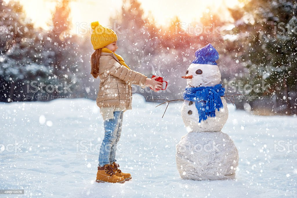 child girl plaing with a snowman stock photo
