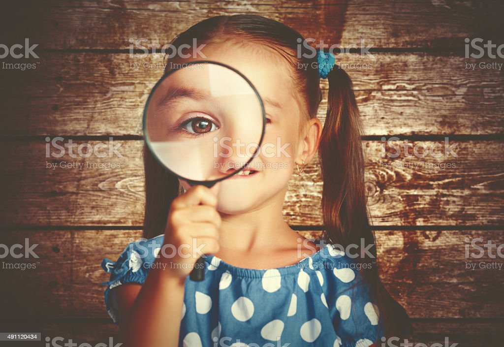 child girl playing with magnifying glass in detective stock photo