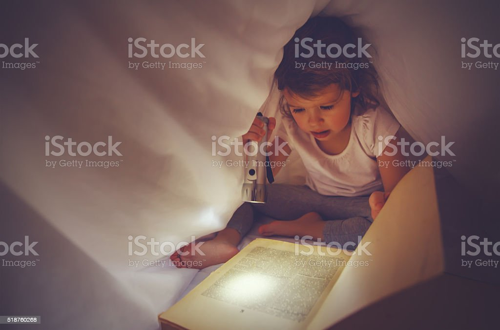 child girl reading  book in dark, under covers in bed stock photo
