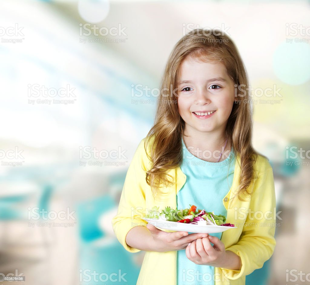 Child girl smiling carry plate salad in cafe background. stock photo