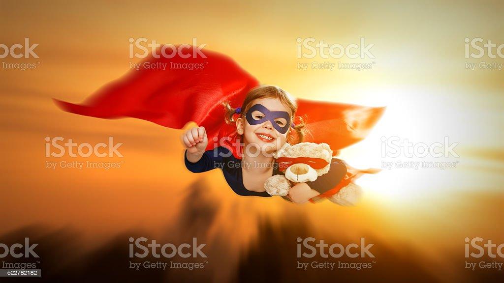 child girl superhero with teddy bear flying through sky stock photo