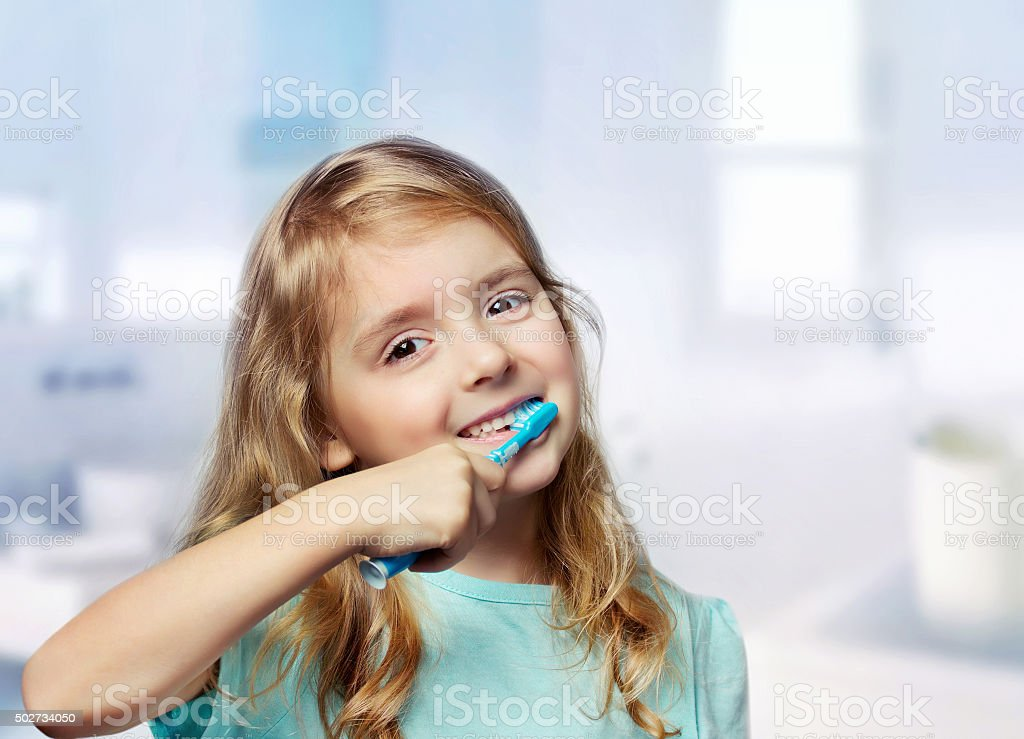 Child girl toddler cleaning teeth in bathroom background. stock photo