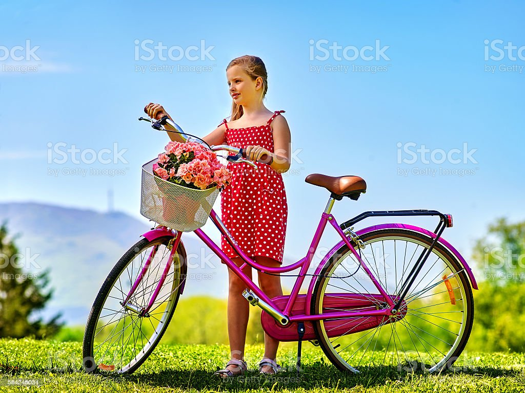 Child girl wearing sundress rides bicycle into park. stock photo