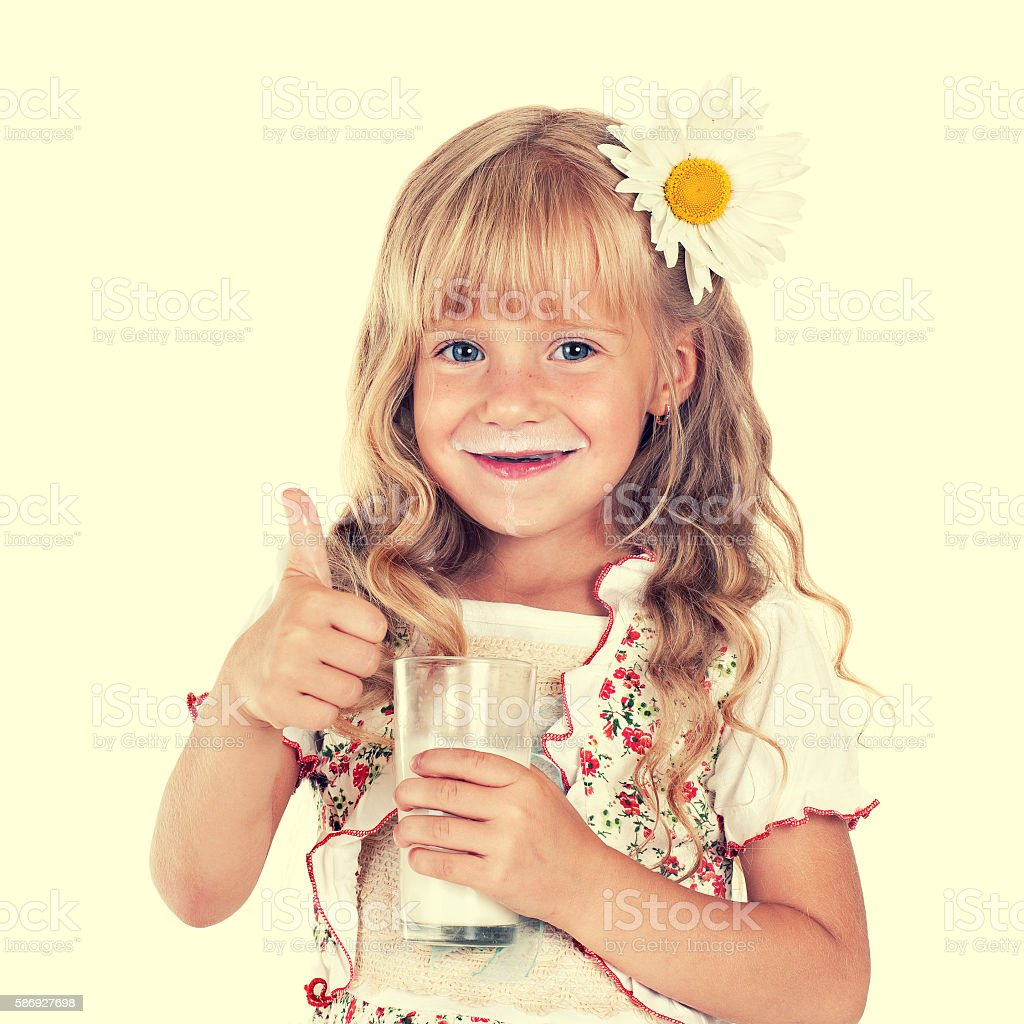 child girl with thumb up drinking milk from glass stock photo