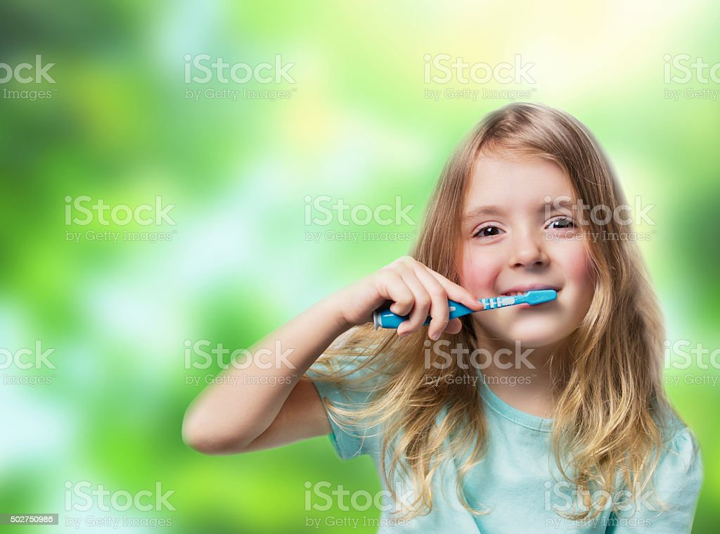 Child girl with toothbrush on green nature background. Dental background. stock photo