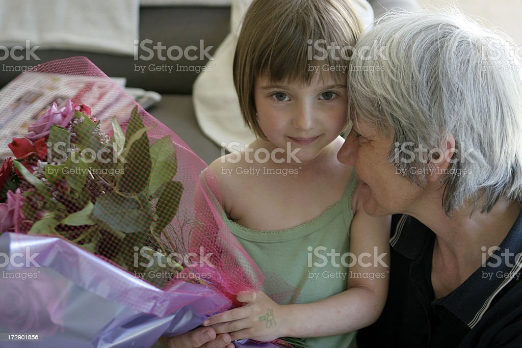 Child giving bouquet to senior woman royalty-free stock photo