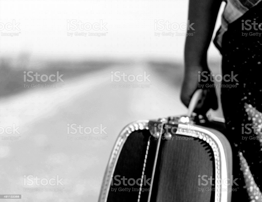 Child goes on the road with her suitcase stock photo