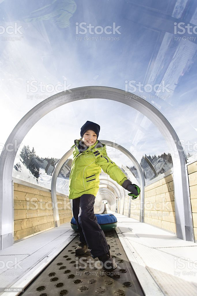 Child going up after snow tubing stock photo
