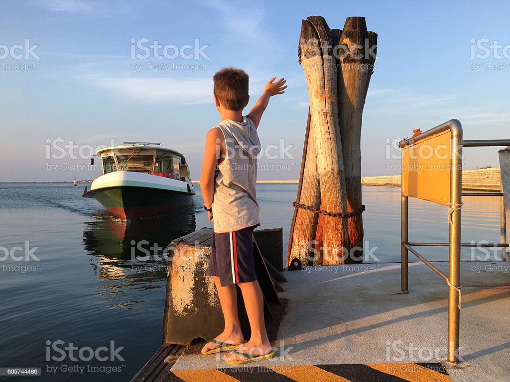 Child greets with his hand an ship stock photo