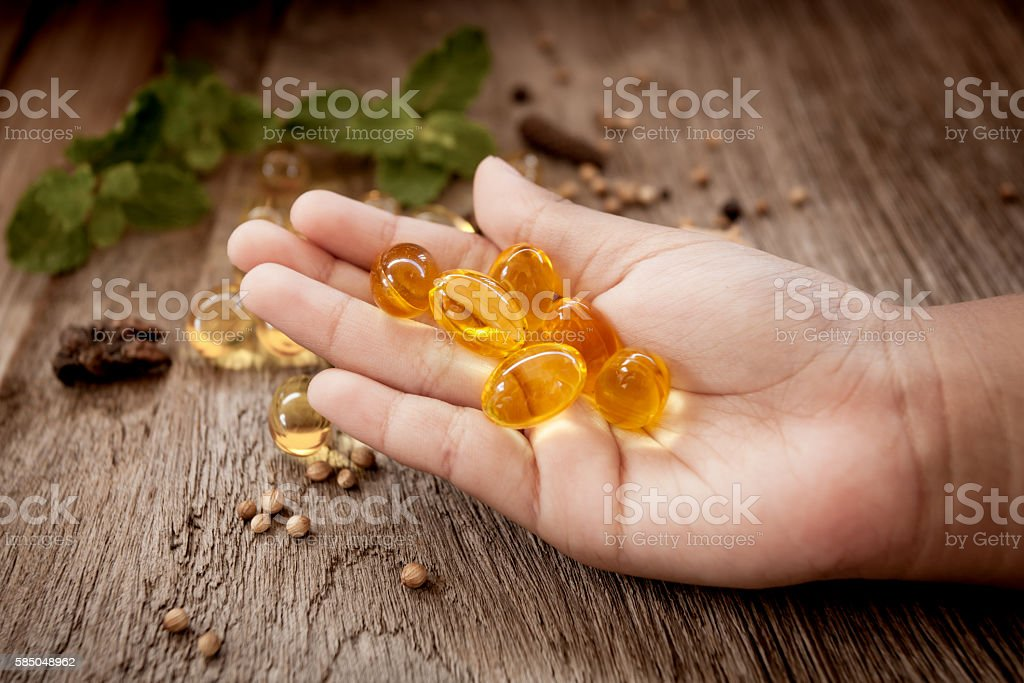 Child hand hold Cod liver oil omega 3 gel capsules stock photo