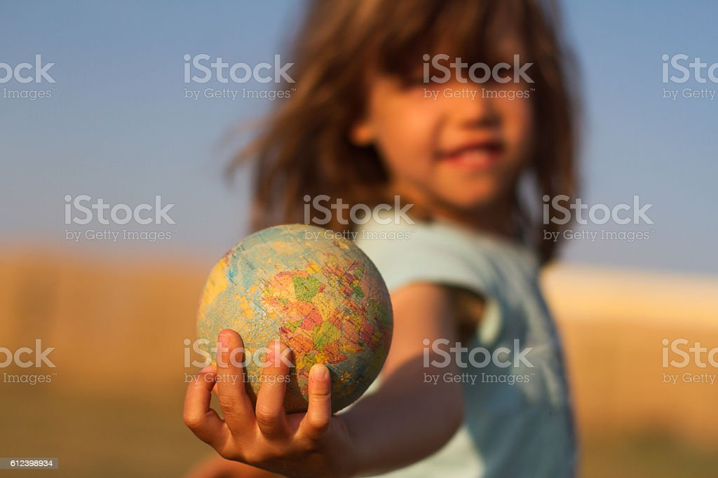 Child hand holding an earth toy globe stock photo