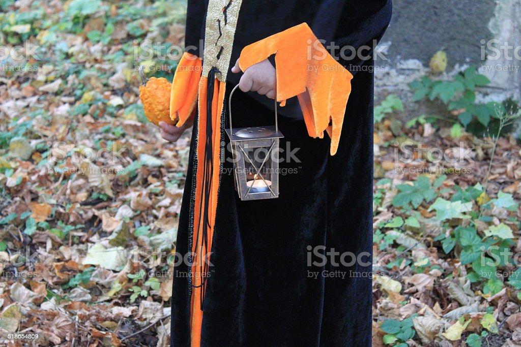 Child hand holding small orange pumpkin and lantern stock photo