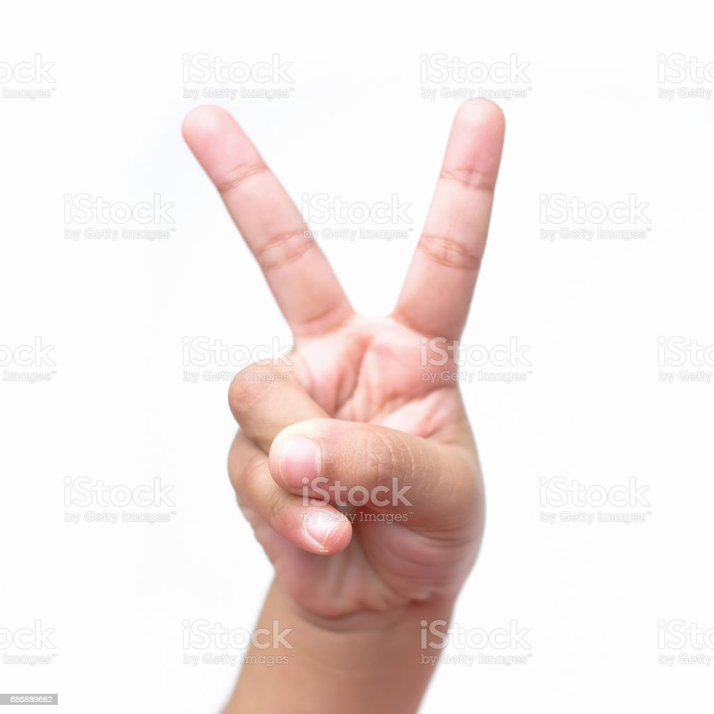 Child hand making victory sign, isolated on a white background stock photo