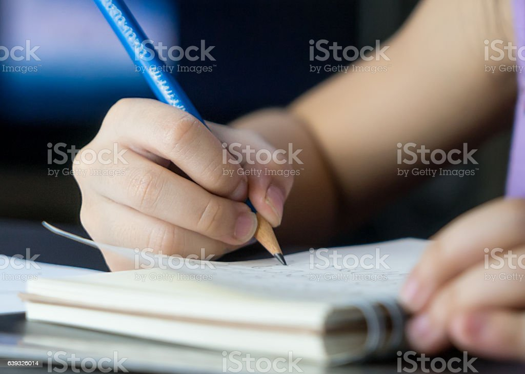 Child hand using pencil to practice writing on a book. stock photo