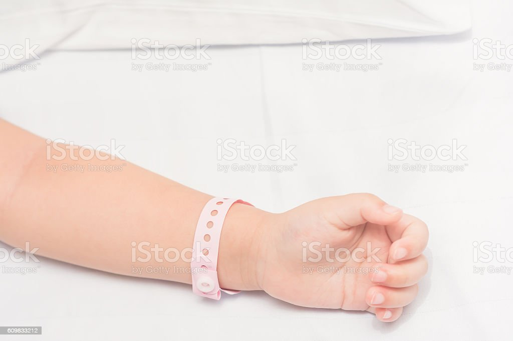 Child hand with Patient id bracelet. stock photo