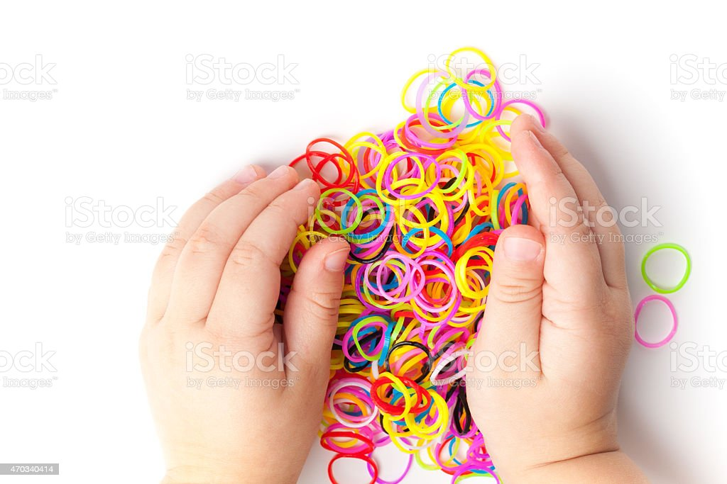 Child hands and pile of small colorful rubber bands stock photo