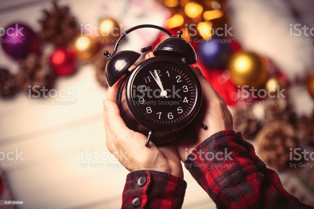 child hands holding a clock stock photo