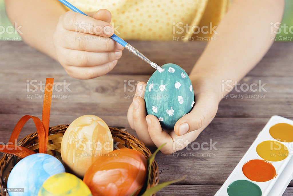 Child hands paint egg stock photo