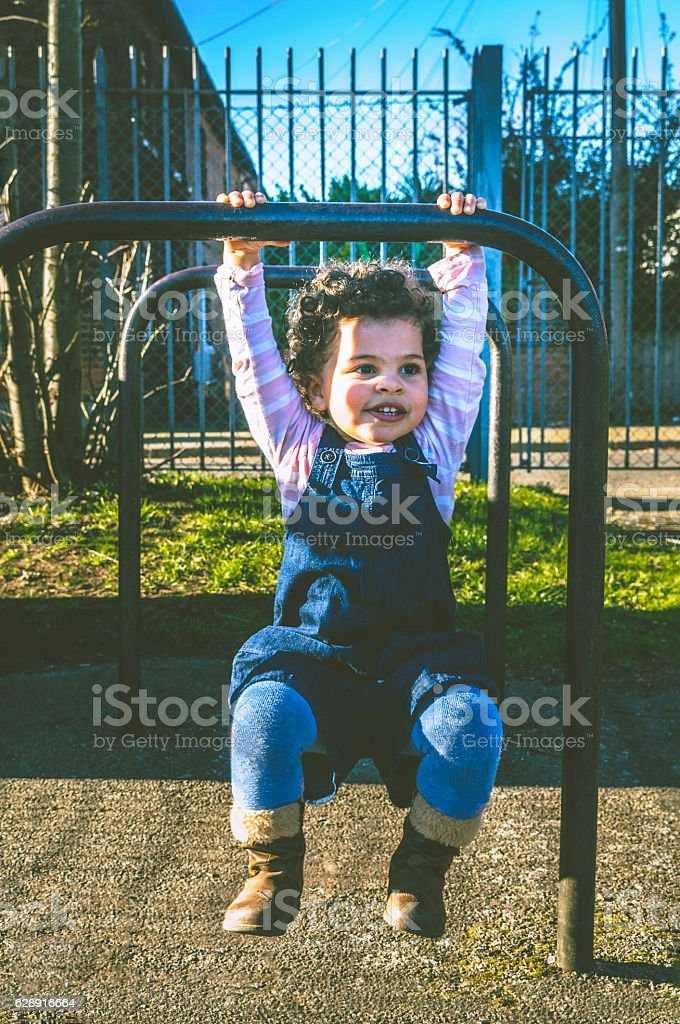 PEOPLE: Child (2-3) Hanging on Bike Stand. stock photo