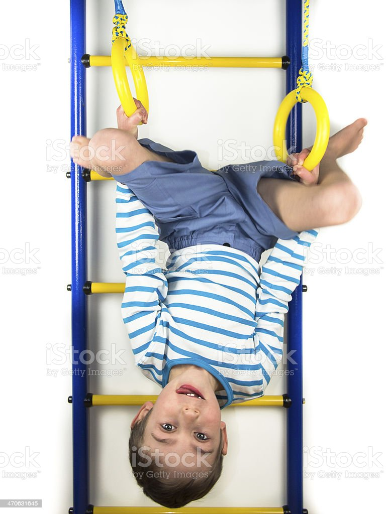 Child hanging upside down on the rings stock photo