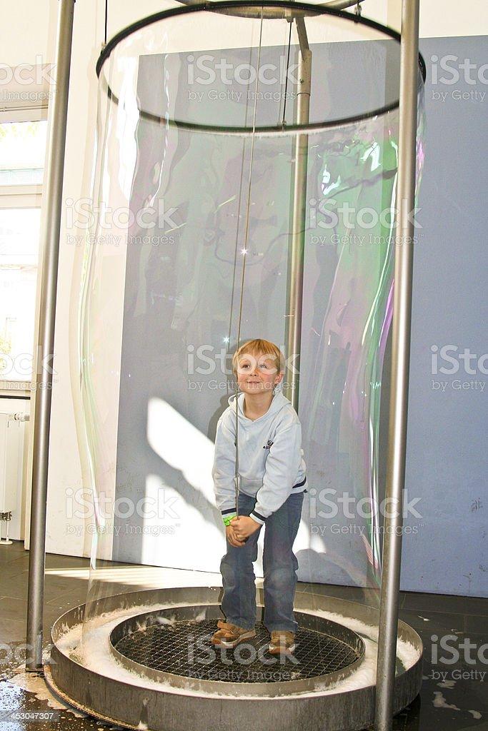 child has fun in a huge bubble machine stock photo