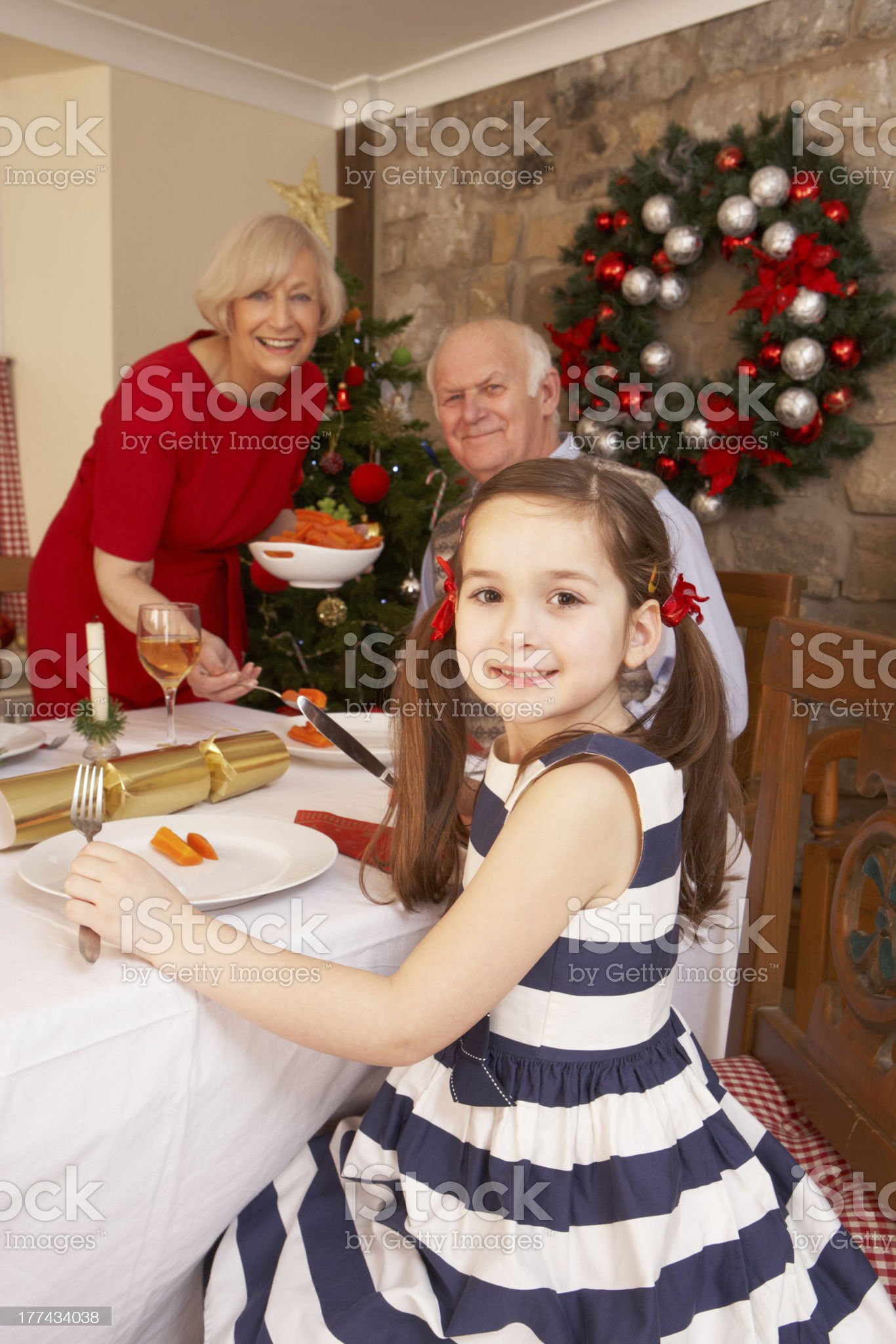 Child having Christmas dinner with grandparents royalty-free stock photo