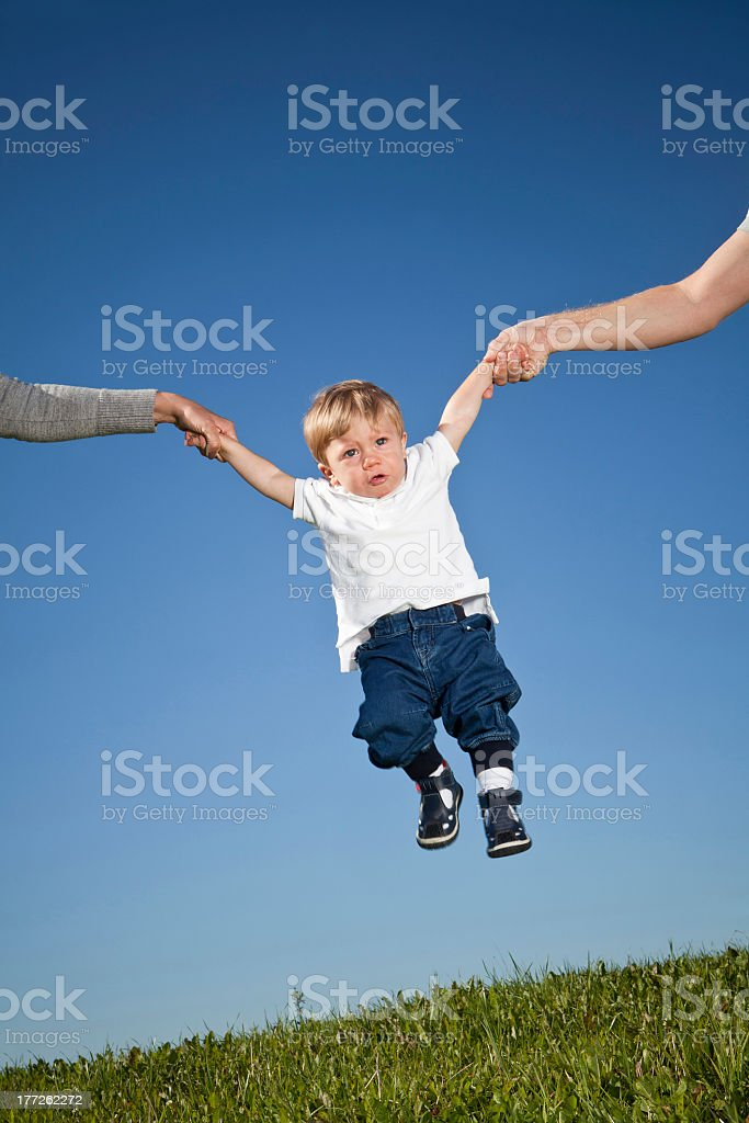 Child held in air by the hands by parents outdoors royalty-free stock photo